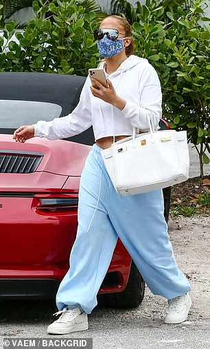 JLo wore her long hair tied in a ponytail and carried a large white leather bag