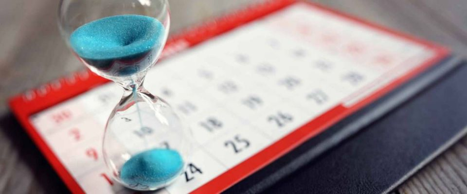 Glass clock concept on calendar for time lost away from important date, schedule and deadline