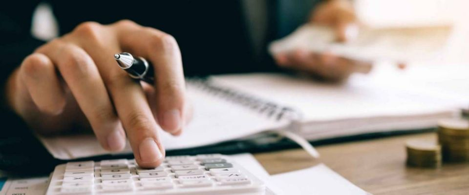 Investors calculate investment costs in a calculator and keep cash notes on hand.